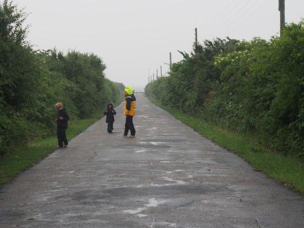 Vi promenerar upp mot byn i regnet